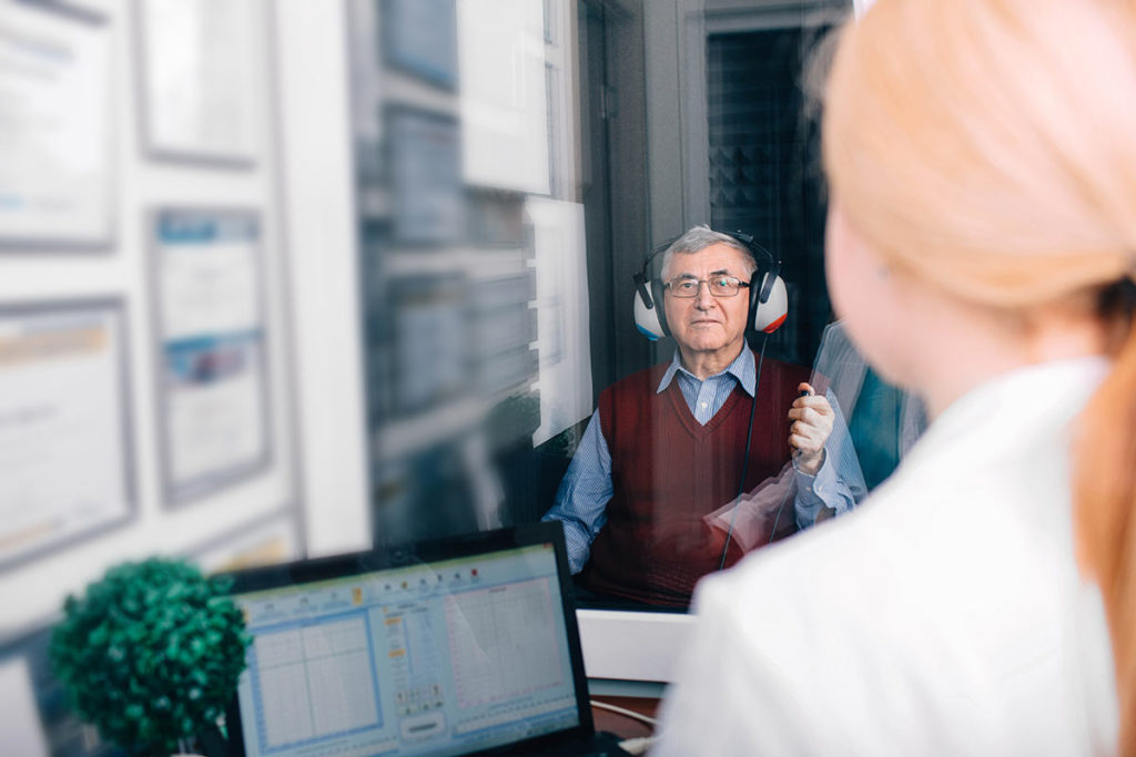man taking a hearing test in isolated room